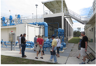 Visitors tour the water plant and look at the blue pipes and two-story white building.